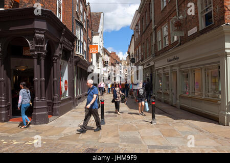 a busy shopping scene in the historic city of york in stonegate with a view of york minster under a blue summer - Stock Photo