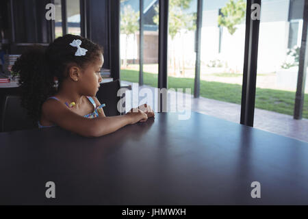 Thoughtful girl sitting at desk in school - Stock Photo