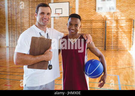 Portrait of smiling coach basketball player standing in court - Stock Photo
