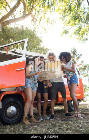 Low angle view of friends looking at map by camper van at campsite - Stock Photo