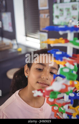 High angle view of elementary student looking at model in classroom - Stock Photo