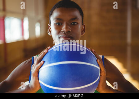 Close up portrait of serious man with basketball standing in court - Stock Photo