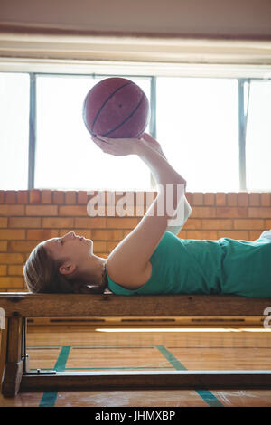 Side view of female player playing with basketball while lying on bench in court - Stock Photo