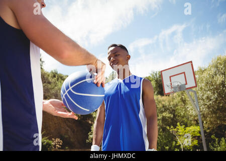 Man showing basketball to friend while playing in court - Stock Photo
