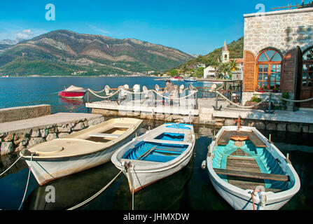 view of three boats in Boka Kotor bay near old restaurant in Tivat, Montenegro - Stock Photo