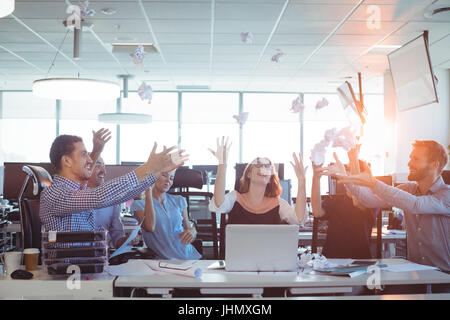 Cheerful business people tossing crumpled paper balls at desk in office - Stock Photo