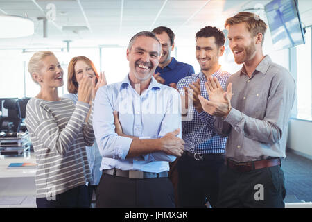 Happy businessman standing with arms crossed while colleagues clapping around him at office - Stock Photo