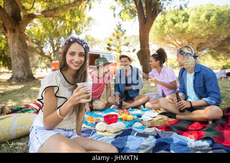Portrait of smiling woman holding drink with friends in background sitting on field during picnic - Stock Photo