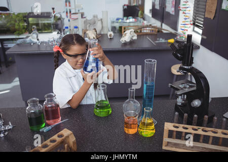 High angle view of elementary student examining blue chemical in flask by desk at science laboratory - Stock Photo