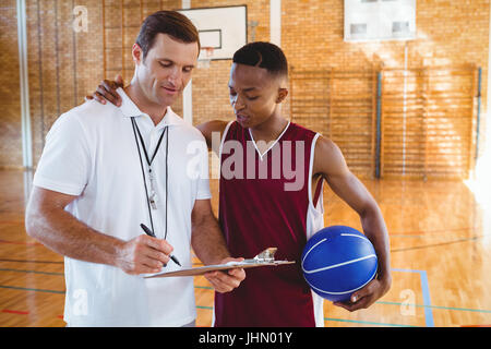 Coach discussing with basketball player while standing in court - Stock Photo