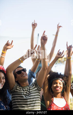 Happy fans dancing with arms raised against sky during music festival - Stock Photo