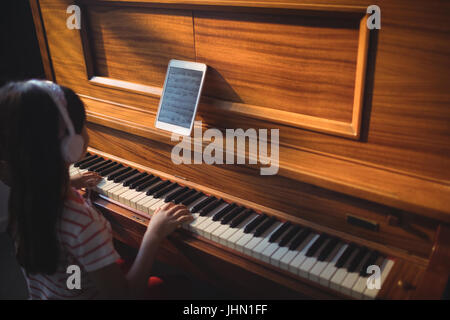 High angle view of girl wearing headphones while practicing piano in classroom at music school - Stock Photo