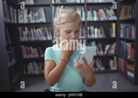 Surprised girl looking at smartphone while standing against bookshelf in library - Stock Photo
