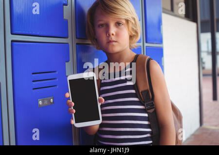 Portrait of boy holding mobile phone while standing by lockers in corridor at school - Stock Photo
