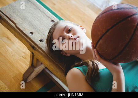 High angle portrait of woman with basketball lying on bench in court - Stock Photo