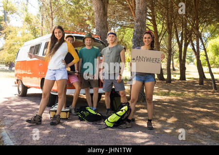 Portrait of friends hitchhiking while standing by camper van - Stock Photo
