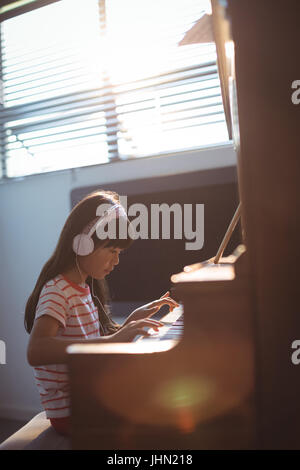 Concentrated girl wearing headphones while practicing piano by window in classroom at music school - Stock Photo