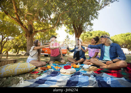 Cheerful friends toasting drink while sitting on field during picnic - Stock Photo