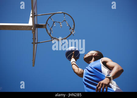 Low angle view of teenage boy playing basketball against clear blue sky - Stock Photo