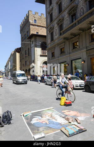 Firenze, Italy - 5 July 2017: people walking in front of a street artwork at Firenze on Italy - Stock Photo