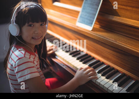 High angle portrait of girl wearing headphones while practicing piano in classroom at music school - Stock Photo