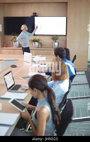 Colleagues at conference table during business meeting in board room - Stock Photo