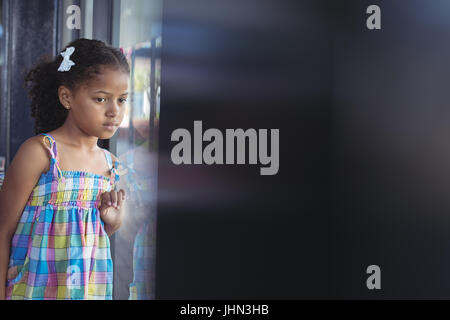 Thoughtful girl looking through window in school - Stock Photo