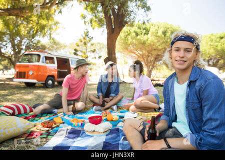 Portrait of smiling man holding drink with friends in background sitting on field during picnic - Stock Photo