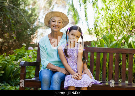 Portrait of senior woman wearing hat sitting with granddaughter on wooden bench at backyard - Stock Photo