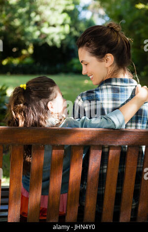 Smiling woman looking at daughter with arm around on wooden bench at backyard - Stock Photo
