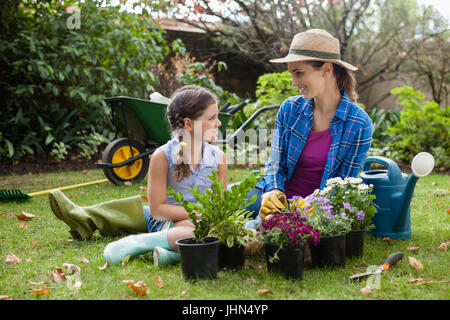 Smiling mother and daughter sitting with various flowering potted plants on field in backyard - Stock Photo