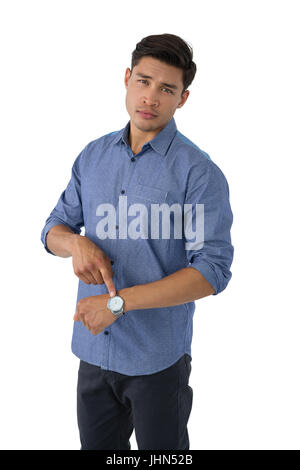 Portrait of young businessman showing time while standing against white background - Stock Photo