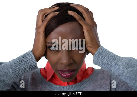 Portrait of frustrated woman with head in hand against white background - Stock Photo