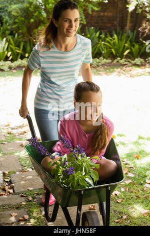 Smiling mother pushing girl with flowers sitting in wheelbarrow at backyard - Stock Photo