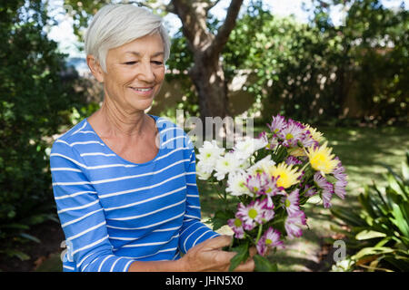 Smiling senior woman holding fresh flower bouquet at backyard - Stock Photo