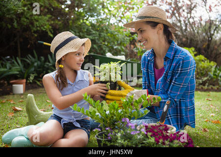Smiling daughter and mother with potted plants sitting on grass in backyard - Stock Photo