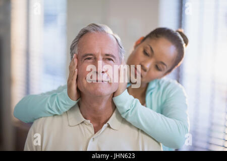 Female therapist holding head of senior male patient at hospital ward - Stock Photo