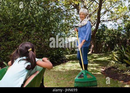 Senior woman holding rake while looking girl sitting in wheelbarrow at backyard - Stock Photo