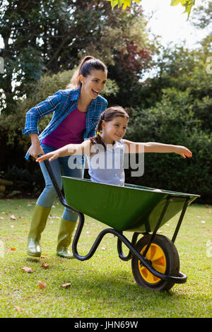 Cheerful mother pushing daughter sitting in wheelbarrow at backyard - Stock Photo