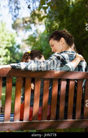 Rear view of mother and daughter sitting with arm around on wooden bench at backyard - Stock Photo