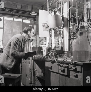 1950s, historical, male research scientist with notebook studies the results of the experiment using the flame propogation apparatus in the science laboratory at Oxford University, Oxford, England, UK.