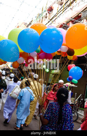 A old lady selling colourful balloons in market of old delhi, Chandni Chowk, On occasion of Eid-Al-Fitr - Stock Photo