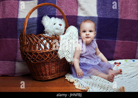 Beautiful little girl in a lilac dress sitting near wicker basket. Toy bear in a basket - Stock Photo