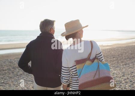 Mature couple looking way on sunset beach - Stock Photo