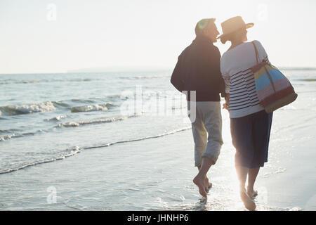 Barefoot mature couple walking on sunset beach - Stock Photo