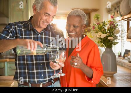 Smiling senior couple pouring white wine in kitchen - Stock Photo