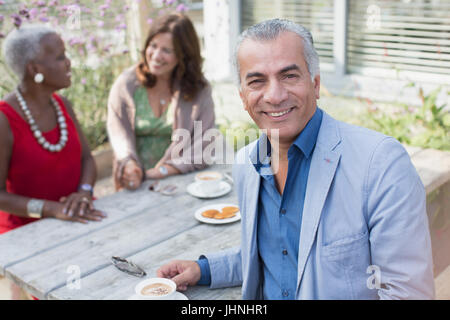 Portrait smiling senior man drinking coffee with friends at patio table - Stock Photo