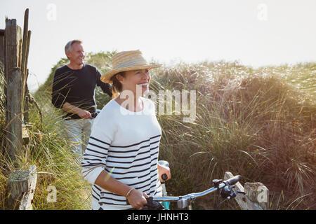 Mature couple walking bicycles along sunny beach grass - Stock Photo