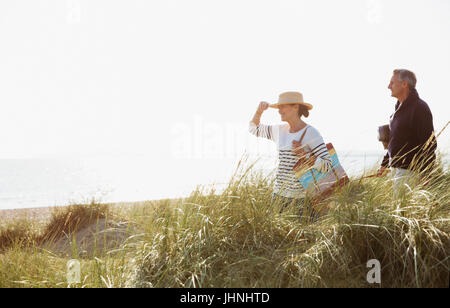Mature couple walking in sunny beach grass - Stock Photo