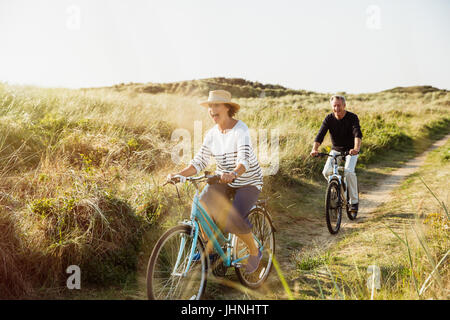 Playful mature couple riding bicycles on sunny beach grass path - Stock Photo